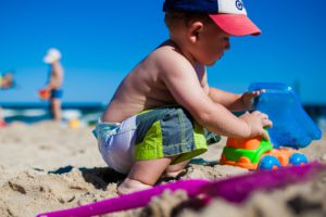 boy digging in sand at beach